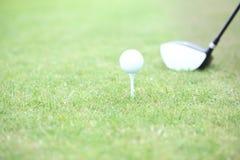 Närbild av golfklubben och utslagsplatsen med bollen på gräs Arkivfoton