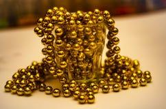 Närbild av guld- pärlor i ett exponeringsglas med en färgbotten med en mjuk suddig bakgrund royaltyfria foton