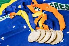 Närbild av guldmedaljer på brasiliansk flagga Fotografering för Bildbyråer