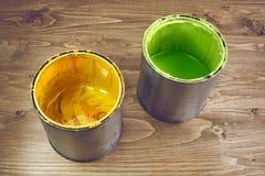 Närbild av guling- och gräsplanmålarfärgcans Arkivfoto
