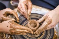 Närbild av händer av den yrkesmässiga manliga keramikern som undervisar hans kvinnliga lärling royaltyfri fotografi