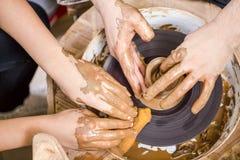 Närbild av händer av den yrkesmässiga manliga keramikern som undervisar hans kvinnliga vän arkivfoto