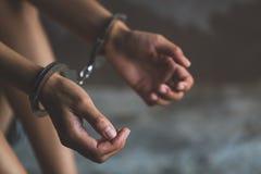 Närbild av händer i handbojan, kvinnlig fånge, arresterad kvinna arkivfoto