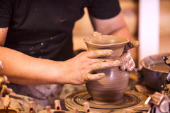 Närbild av händer som gör krukmakeri på ett hjul Arkivbild