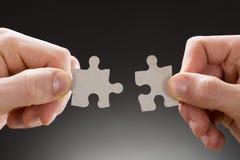 Närbild av händer som rymmer figursågstycken Fotografering för Bildbyråer