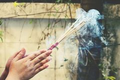 Närbild av händer som rymmer som röker brinnande rökelsepinnar arkivfoto