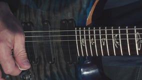 Närbild av händer som spelar elbasen materiel Manliga händer av gitarristen som spelar ackord på elbasen Musik utförde på fotografering för bildbyråer