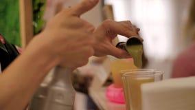 Närbild av händerna av bartendern på arbete Bartendern häller fruktsaften från järnbunten i koppar arkivfilmer