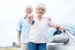 Närbild av händerna av en hög kvinna som visar tangenterna av hennes bil arkivbild