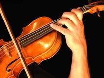 Närbild av händerna av en violinist som spelar hans instrument arkivfoton