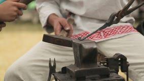 Närbild av händerna av hovslagaren och hans elev med hammarna som slår den glödande metallen stock video