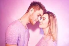 Närbild av härligt kyssa för par Lycklig man och flicka som trycker på med deras näsor i rosa bakgrund Stående av älska Arkivbilder