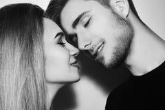 Närbild av härligt kyssa för par Lycklig man och flicka som trycker på med deras näsor svart white Arkivbilder