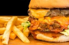 Närbild av hamburgaren på svart bakgrund Grillad kött och ost Arkivbilder