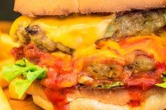 Närbild av hamburgaren på svart bakgrund Grillad kött och ost Royaltyfri Bild