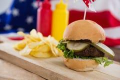 Närbild av hamburgaren på träbräde Arkivbilder