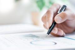 Närbild av handaffärsmanläsning och handstil med det undertecknande avtalet för penna över dokumentet för att avsluta ansökningsb arkivfoton