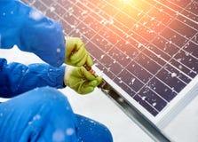 Närbild av handarbetaren som installerar solpaneler i snöig väder Arkivbilder