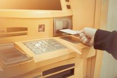 Närbild av handen för kvinna` som s sätter in debiteringkortet in i en ATM-machin arkivbilder