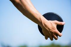 Närbild av handen som rymmer en diskus Arkivfoton