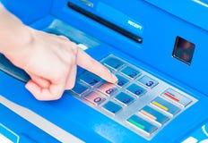 Närbild av handen som skriver in PIN-/passkod på blått ATM-/bankmaskintangentbord royaltyfri fotografi