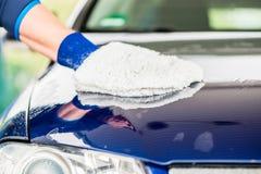 Närbild av handen som torkar bilen med microfiberwashkardan Royaltyfri Fotografi