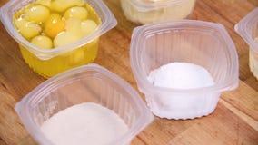 Närbild av ingredienser i koppar för framställning av söta bakelser Materiell?ngd i fot r?knat Rå ingredienser står separat i pla stock video