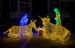 Närbild av juljulkrubban exponerad med kulöra ljus royaltyfri bild