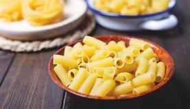 Närbild av kökbehållare med macaroniien omkring som ska lagas mat på trätabellen Fotografering för Bildbyråer