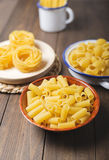 Närbild av kökbehållare med makaroni och spagetti omkring som ska lagas mat på trätabellen Arkivfoton