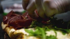 Närbild av kocken som förbereder italiensk pizza Ram Den yrkesmässiga kocken med handskar sätter på stycken av skinka på pizza me lager videofilmer