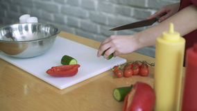 Närbild av kocken som hugger av en gurka med röd peppar på skärbrädan 4k arkivfilmer