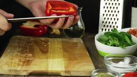 Närbild av kocken som hugger av en morot med röd peppar på skärbräda lager videofilmer