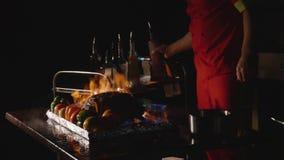 Närbild av kocken som lagar mat en huvudsaklig bankettmaträtt Grönsaker och kött med brandshow arkivfilmer