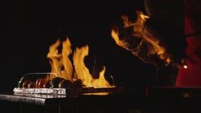 Närbild av kocken som lagar mat en huvudsaklig bankettmaträtt Grönsaker och kött med brandshow stock video