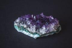 Närbild av kristaller för ametiststendruse på den polerade tjock skiva för mörk granit Textur av kristaller av ametistametist royaltyfri foto