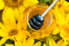 Närbild av kruset som är full med honung och honung-skeden i mitt av solrosor arkivbild