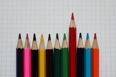 Närbild av kulöra blyertspennor på vitbok royaltyfri foto