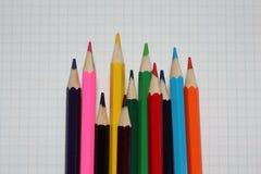 Närbild av kulöra blyertspennor på vitbok royaltyfri fotografi