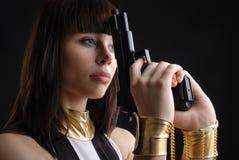 Närbild av kvinnan i handbojor med en handeldvapen. Arkivbild