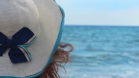 Närbild av kvinnan i hatt som kopplar av på den soliga stranden på sjösidan som tycker om seascape stock video