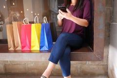 Närbild av kvinnan som använder hennes smartphone under shopping arkivfoton