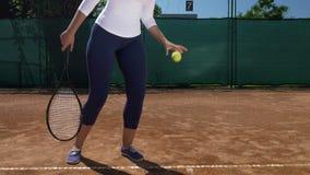Närbild av kvinnan som har en tennisracket i hand och med den annan handen som studsar en boll på askan stock video