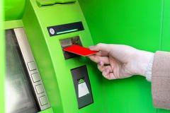 Närbild av kvinnan som ler kvinnan som återtar pengar från kreditkort på ATM arkivfoton