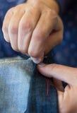 Närbild av kvinnas att sy för händer Arkivfoto