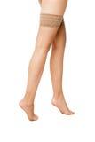 Närbild av kvinnas ben i beigea slangar Fotografering för Bildbyråer