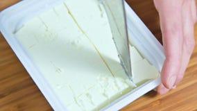 Närbild av kvinnliga händer som klipper en kniv i en packe av vit fetaost in i kuber för grekisk sallad arkivfilmer