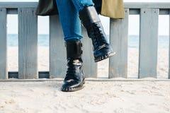 Närbild av kvinnligben i svartkängor och jeans arkivfoto