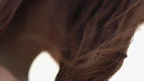 Närbild av långt brunt lockigt hår och den nakna skuldran av den unga kvinnan i blåsig dag arkivfilmer