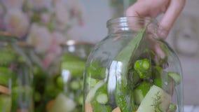 Närbild av lögner för en hand för kvinna` s i en Glass krus med grönsaker för marinadblad av grönska lager videofilmer